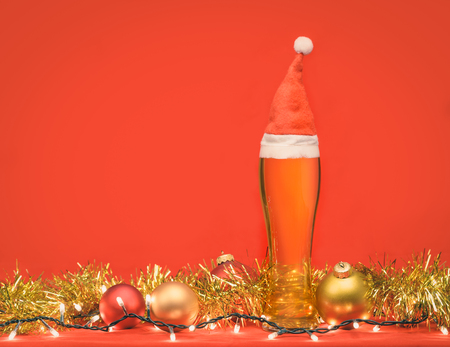 Close-up shot of full pilsner glass of pale lager beer or ale with Santa Claus or christmas red hat, christmas lights baubles and tinsel on red background