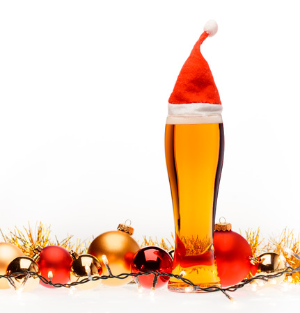 Full pilsner glass of pale lager beer or ale with Santa Claus or christmas red hat christmas baubles lights and tinsel on white background Standard-Bild - 113610765