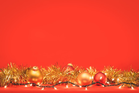 Christmas baubles with golden tinsel and christmas lights on red background Standard-Bild - 113610766