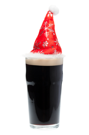 Nonik pint glass of dark beer or stout ale with red christmas or santa claus hat on white background Standard-Bild - 113610768