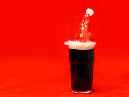 Nonik pint glass of dark beer or stout ale with red santa hat on red christmas background Standard-Bild - 113610770