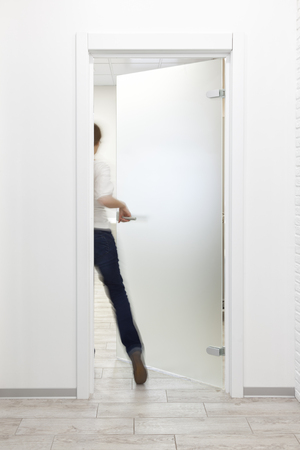 Young woman entering a room in modern office with minimalist white interior through frosted glass door. Woman is motion blurred Standard-Bild - 113610843