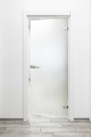 Minimalist modern office interior with white wall and frosted glass door ajar 免版税图像 - 113610844