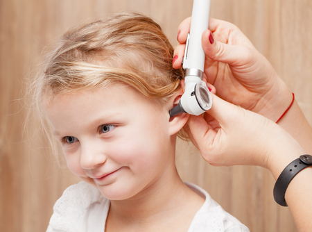 Female pediatrician examines little girls ear. Doctor using a otoscope or auriscope to check ear canal and eardrum membrane. Child ENT check concept Stock Photo