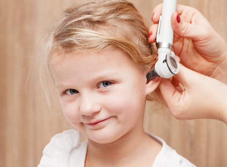 Female pediatrician examines little girl's ear. Doctor using a otoscope or auriscope to check ear canal and eardrum membrane. Child ENT check concept Standard-Bild - 113610848