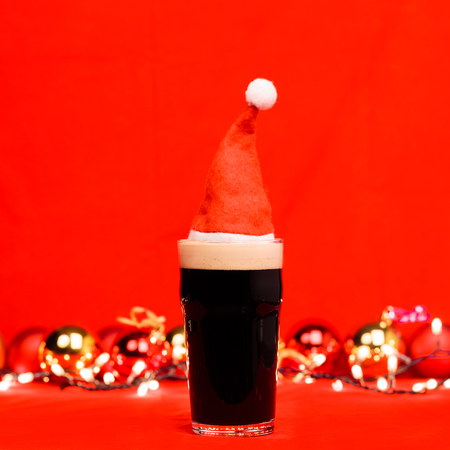 Nonik pint glass of dark beer or stout ale with red santa hat christmas lights baubles and on red background Stock Photo