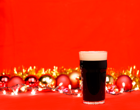 Nonik pint glass of dark beer or stout ale with christmas lights baubles and tinsel on red background Standard-Bild - 113610854