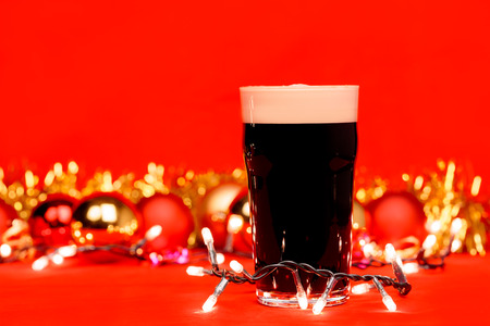 Nonik pint glass of dark beer or stout ale with christmas lights baubles and tinsel on red background Standard-Bild - 113610855