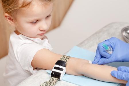 Doctor or nurse disinfecting little girl's arm preparing to take a blood sample from her vein. Pediatric venipuncture or venepuncture procedure Standard-Bild - 113610910