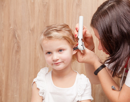 Female pediatrician examines little girl's ear. Doctor using a otoscope or auriscope to check ear canal and eardrum membrane. Child ENT check concept Standard-Bild - 113610912