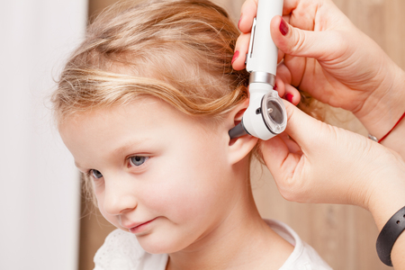 Female pediatrician examines little girl's ear. Doctor using a otoscope or auriscope to check ear canal and eardrum membrane. Child ENT check concept Standard-Bild - 113610915