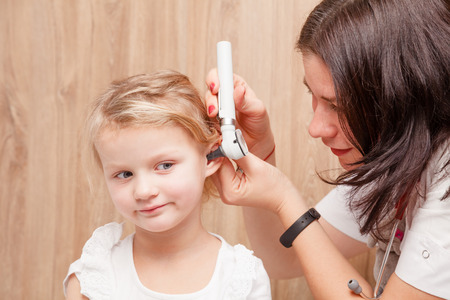 Female pediatrician examines little girl's ear. Doctor using a otoscope or auriscope to check ear canal and eardrum membrane. Child ENT check concept Standard-Bild - 113610919