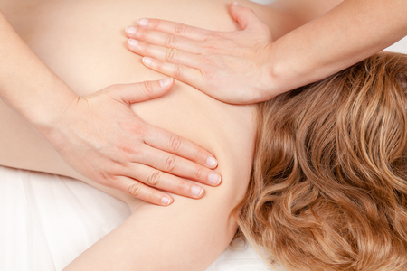 Tween age girl's shoulder being manipulated by osteopathic or chiropractic manual therapist or physician - medical massage concept Standard-Bild - 113610921