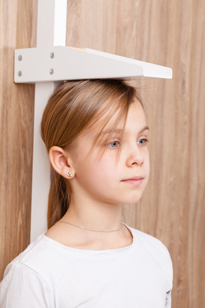 Portrait of cute preteen girl during stature measurement  with stadiometer - child check-up concept Standard-Bild - 113611002