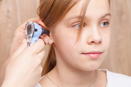 Female pediatrician examines elementary age girl's ear. Doctor using a otoscope or auriscope to check ear canal and eardrum membrane. Child ENT check concept Standard-Bild - 113611009