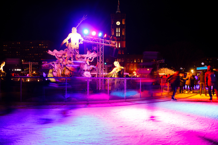 People skating on ice rink at Christmas Market in Mitte, Central Berlin, Germany at night. Skaters are blurred in motion. Red City Hall (Rotes Rathaus) is seen in background Imagens