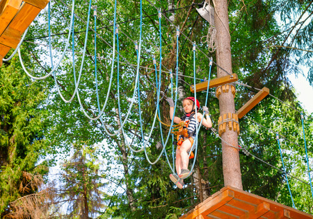 Brave elementary age girl wearing safety harness climbing at a ropes course in outdoor treetop adventure park in a summer forest passing hanging rope bridge obstacle