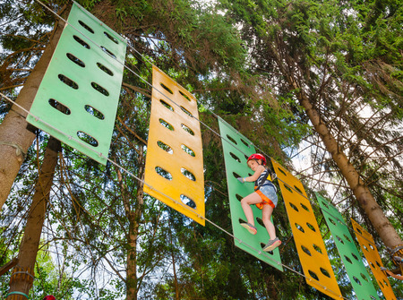 Elementary age girl wearing safety harness passing rope bridge obstacle at a ropes course in outdoor treetop adventure park Stock Photo