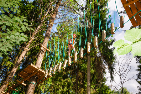 Elementary age girl wearing safety harness passing unstable rope bridge obstacle at a ropes course in outdoor treetop adventure park Stock Photo