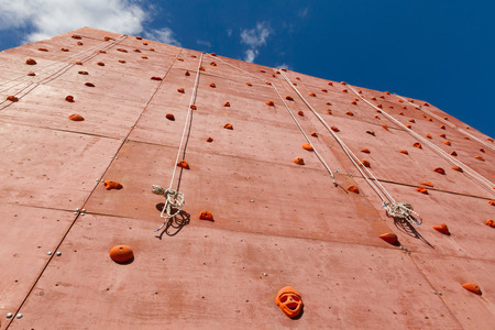 Artificial rock climbing wall with grips for hands and feet in outdoor adventure park used to practise lead climbing or bouldering