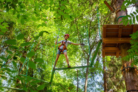 Teenager boy wearing safety harness passing Z-shaped balance beam obstacle at a ropes course in outdoor treetop adventure park