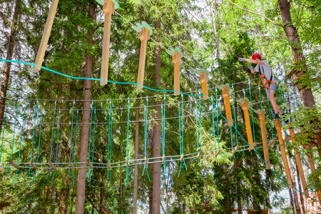 Teenager boy wearing safety harness passing hanging rope bridge obstacle at a ropes course in outdoor treetop adventure park