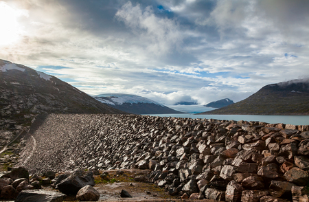 Rock armoured dam at Styggevatnet glacial lake with Austdalsbreen glacier seen in background, Jostedalsbreen National Park, Sogn og Fjordane, Norway, Scandinavia