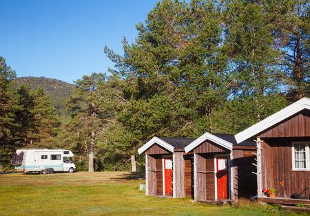 Wooden cabins at norwegian campsite with parked campervan seen in background, Norway, Scandinavia Standard-Bild - 118216744