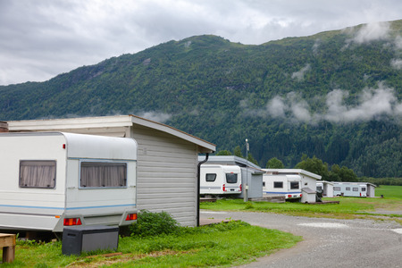 Grey wooden cabins with parked camper trailers at a campsite in Norway, Scandinavia. Cloudy moutain is seen in background Stockfoto - 118216747