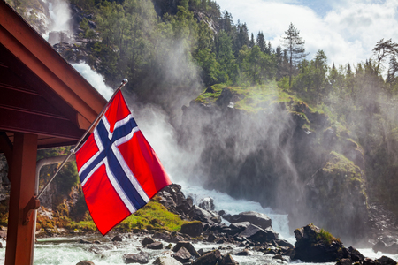 Norwegian flag against rushing Latefoss (Latefossen) twin waterfall, a popular tourist attraction in Odda, Hordaland county, Norway, Scandinavia Imagens