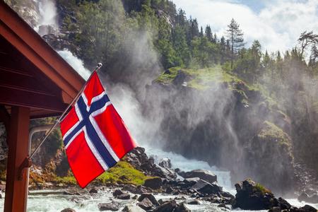 Norwegische Flagge gegen rauschenden Latefoss (Latefossen) Zwillingswasserfall, eine beliebte Touristenattraktion in Odda, Kreis Hordaland, Norwegen, Skandinavien