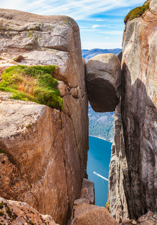 Kjeragbolten boulder, a glacial deposit wedged in the mountains crevasse at the edge of Kjerag (or Kiragg) Plateau, a popular travel destination in Forsand municipality of Rogaland county, Norway, Sca 写真素材