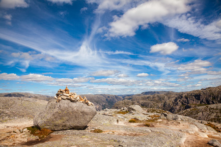 Cairn (a pile of stones) marking mountain hiking trail along the Lysefjord at Kjerag (or Kiragg) Plateau, a popular travel destination in Forsand municipality of Rogaland county, Norway, Scandinavia Standard-Bild - 118216978