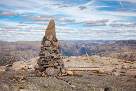 Cairn (a pile of stones) marking mountain hiking trail along the Lysefjord at Kjerag (or Kiragg) Plateau, a popular travel destination in Forsand municipality of Rogaland county, Norway, Scandinavia Standard-Bild - 118217085