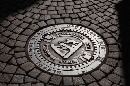 STAVANGER, NORWAY - AUGUST 14, 2018: Cast iron manhole cover on a cobblestone street in the city center