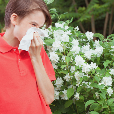 Teenager boy with seasonal influenza blowing his nose on a tissue in a spring garden -  seasonal infection concept 写真素材
