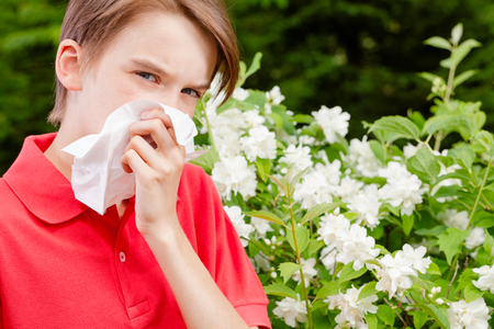 Teenager boy with seasonal influenza blowing his nose on a tissue in a spring garden -  seasonal infection concept Stock fotó