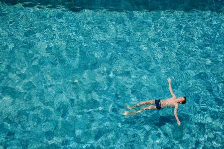 Teenager boy floating on water in a hotel swimming pool enjoying summer holidays Standard-Bild - 118201693
