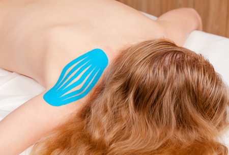 Shoulder with blue elastic therapeutic tape applied for treating pain and disability from athletic injury or other physical disorder - Kinesiotaping concept Standard-Bild - 118201718