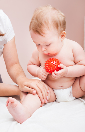 Seven month baby girls knee joint being manipulated by osteopathic or chiropractic manual therapist in a pediatric clinic. Child is holding rubber toy in hand looking at what doctor does