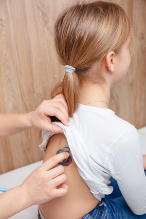 Female pediatrician examines elementary age girl's back in pediatric clinic. Doctor using a stethoscope to check heart beat and lungs. Child check-up concept Standard-Bild - 118202194