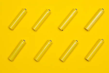 Top view yellow AAA alkaline batteries colorful pop art style flat lay photo pattern Stock Photo