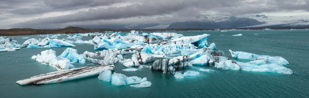 Panoramic view of melting icebergs floating in the Jokulsarlon glacial lagoon, a popular travel dastination and one of the natural wonders of Iceland with Breidamerkurjokull glacier tongue seen in bac