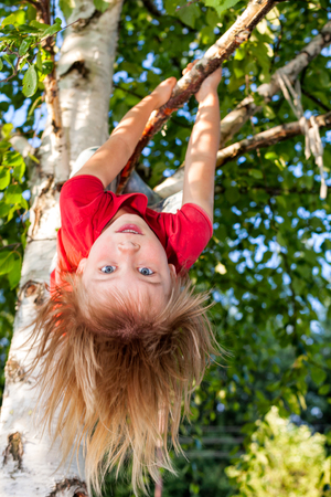 Elementary age girl hanging from a tree branch while playing in a summer garden - child safety or risky play concept