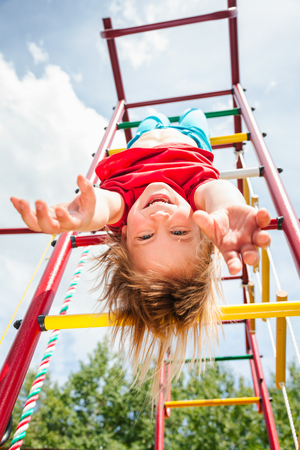 Elementary age girl hanging upside down from a jungle gym (monkey bars or climbing frame) in a playground enjoying summertime