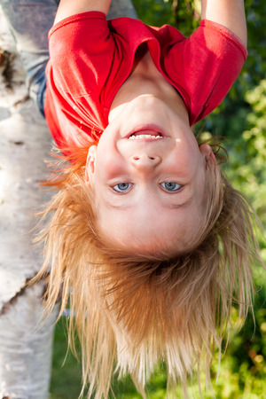 Portrait of happy elementary age girl wearing red tee shirt hanging upside down from a tree branch - summer fun concept