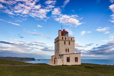 Dyrholay lighthouse (Dyrhólaeyjarviti) located on the Dyrhólaey promontory  near the village of Vík í Mýrdal, a popular tourist attraction on the South Coast of Iceland. Reynisdrangar b