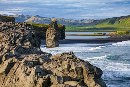 Scenic Icelandic landscape with Arnardrangur (Eagle rock) basalt sea stack on the Reynisfjara black volcanic sand beach near the village of Vík í Mýrdal, a popular tourist attraction on the south c