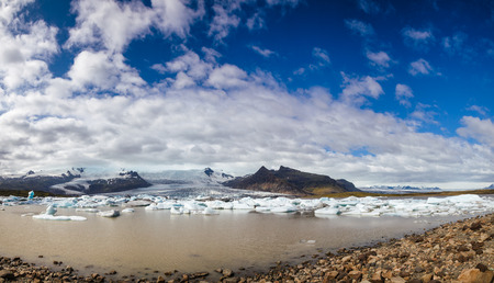 Panoramic view of melting icebergs floating in the Fjallsarlon glacial lake with Fjallsjokull glacier calving into lagoon seen in background, Vatnajokull National Park, Southeastern Iceland, Scandinav 写真素材