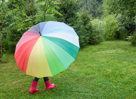 Little girl wearing red rubber boots walking hiding under colorful umbrella in a rain - drizzly weather concept